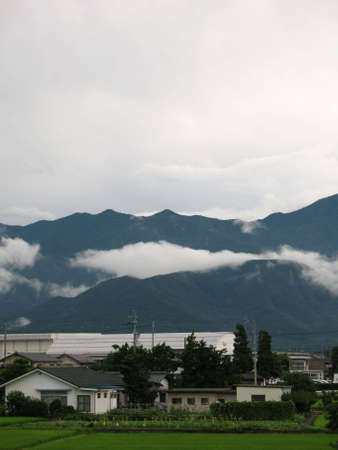 A sleepy Japanese village surrounded by mountains and clouds. Stock Photo