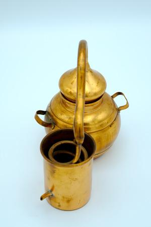 destilacion: Alambique de cobre - Aparato de destilación empleado para la destilación de alcohol, aceites esenciales y alcohol ilegal. destilería de vino de cosecha para la casa hecha del vino aislado en blanco. Foto de archivo