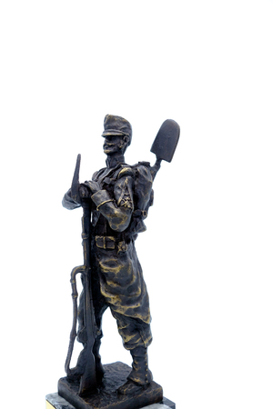 antique rifle: Bronze figurine of a Spanish soldier Sapper nineteenth century with a shovel and a rifle. Isolated Stock Photo