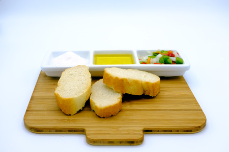 accompanied: Appetizer with salt, olive oil, peppers and onion cut into dice. Accompanied by bread. On white background
