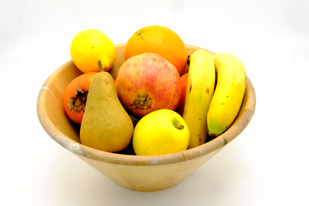 Fruitschaal met sinaasappel, citroen, peer, persimmon, bananen, kiwi en pomegrenade Stockfoto