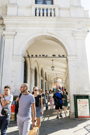 Venice, Veneto  Italy. May 21, 2017: Portals of the Dolfi Manin Palace with people walking and pigeons perched on a bar