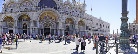 polychrome: Venice, Veneto  Italy- May 21, 2017: Polychrome marble facade of the Basilica di San Marco in Piazza San Marco and people walking by it
