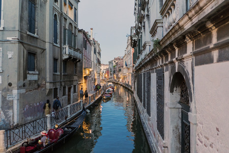 Channel called Rio Marin and anchorage called Garzotti at dusk with people walking and gondolas in Venice, Italy