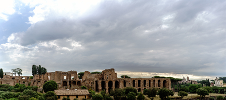 Archaeological ruins of the Severian Arcades on the Palatine and temple of Apollo Palatine with a sky with many clouds. View from the street called Viale Aventino in Rome, Italy