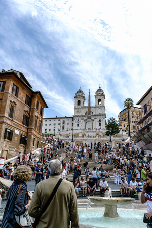Rome, Lazio, Italy. May 22, 2017: View from the Spanish steps of the staircase called Scalinata di Trinità dei Monti, at the top of the building is the Salustian obelisk and the Church called Trinita dei Monti. Full of people and with a little cloudy Editorial