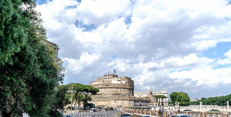 Rome, Lazio, Italy. May 25, 2017: Bridge over the river Arno called San Angelo full of people strolling, in the background the national museum of the castle of San Angelo and a blue sky with a cloud over the castle Editorial