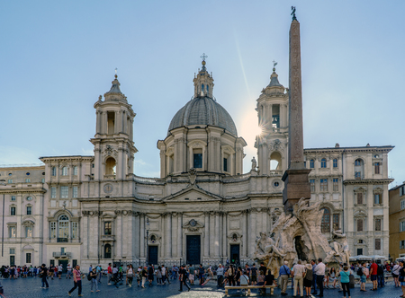 touristy: Rome, Lazio, Italy. July 25, 2017: Main facade of the church called Santa Agnes in Agony SantAgnese in Agone and source called Fontana dei Fiumi or the four rivers in the famous square of Navona with people walking and a very blue sky located In the  Editorial