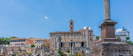 View of the various ruins of the Roman Forum with a very blue sky slightly cloudy without people in sight Stock Photo
