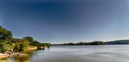 Panoramic view of a lake formed by a marsh called Cecebre in Galicia (Spain) with vegetated banks, mainly trees Stock Photo