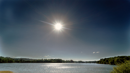 Backlit view of a lake formed by a marsh called Cecebre in Galicia (Spain), with sun in sight