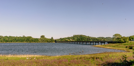 Panoramic view of a lake and its shores formed by the Cecebre reservoir in Galicia (Spain). On the right the bridge that crosses it looks