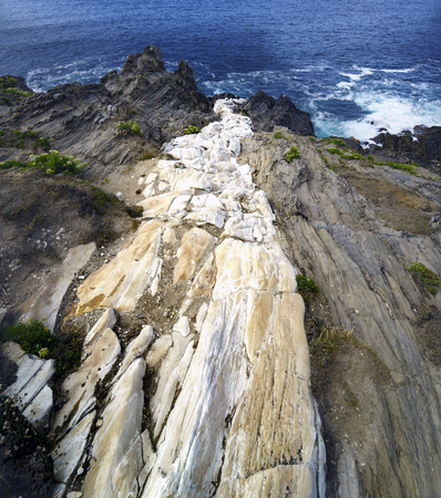 White stone streak that empties into the sea on a cliff of gray stones called Seixo Branco in Coruna, Spain Stock Photo