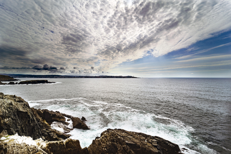 Extra wide-angle panoramic view of the Atlantic coast of La Coruna with the city in the background and some clouds that direct the view towards it 版權商用圖片