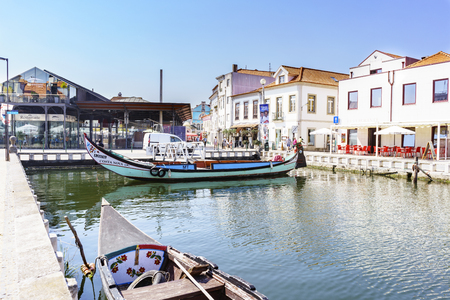 eiro  Portugal August 13, 2017. Channel with the boats called moliceiros seen from the street called Cais dos Botiroes with the terrace of a bar. In the background, the fish market. Very blue sky Editorial