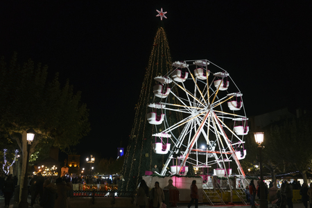 Alcala de Henares, Madrid, Spain / December 1, 2017: Night photo of a children's ferris wheel and a Christmas tree placed for Christmas parties in the square called