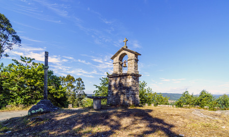 bell tower and stone cross on the top of the hill called La Espenuca in Galicia (Spain).Clear sky with some clouds. Without people Stock Photo
