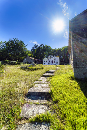 Backlight of a building of pierdra (Chapel) and small cemetery with a stone path to avoid the mud when it rains. With typical Atlantic vegetation, very green and a very blue sky, no people Stock Photo