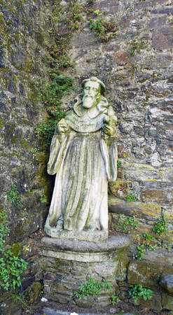 ontedeume, Galicia  Spain. July 29, 2017. Ancient medieval stone statue depicting Saint James in front of a stone wall