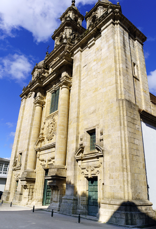 Facade of the parish church of Santiago in neoclassical style with baroque reminiscences built in granite stone in a village called Pontedeume in La Coruna, Spain. With a blue sky