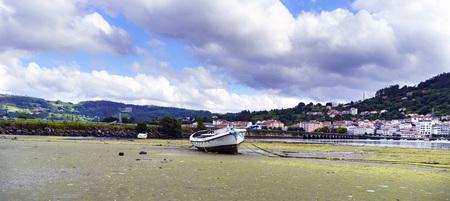 Barco varado en una playa de arena durante la marea baja. La ciudad de Pontedeume en Galicia, España en el otro lado de la ría de Eume y la vista del puente de piedra que lo cruza Foto de archivo - 92707561