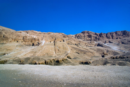 Hillside at the exit of the valley of the kings with the entrance of one of the tombs in sight and without any vegetation. Without tourists