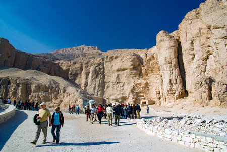 Valley of the Kings, Egypt. February 18, 2017: Tourists visiting the valley with a background of very arid vertical rock walls. View of the valley floor Editorial