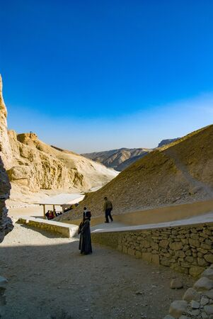 Valley of the Kings, Egypt. February 18, 2017: View of the valley floor with an Egyptian dressed in a djellaba and smiling. Surrounded by the slopes. Very arid and impressive mountains