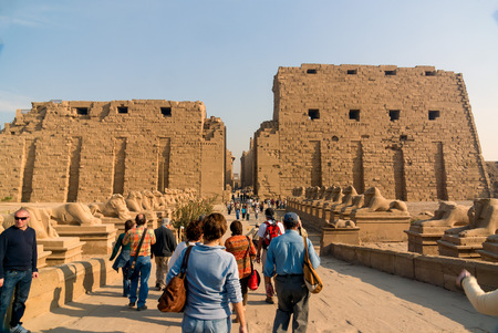 Luxor, Egypt. February 20, 2017: Entrance and well-preserved facade of the Egyptian karnak temple surrounded by sphinxes and view of many tourists going in and out to visit it