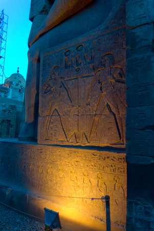 Illuminated wall with hieroglyphics of the Karnak temple representing two human figures working. Photo at dusk and without people