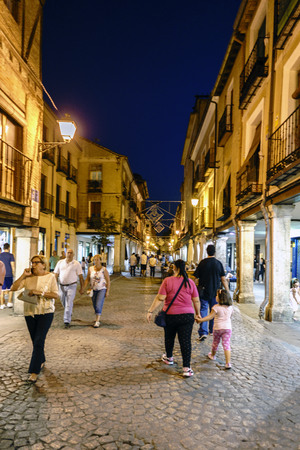 Alcala de Henares, Madrid, Spain. September 8, 2017; Night view of the main street of the town called Mayor cobblestone and with facades of old houses and arcades very illuminated and with many people walking