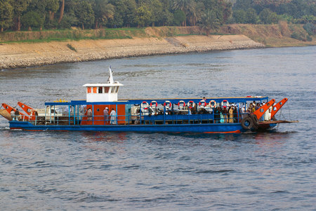 Nile River, near Aswnm, Egypt, February 21, 2017: Ferry transporting people crossing the Nile River and full of Arabian Egyptians with djellaba and turbans Editorial