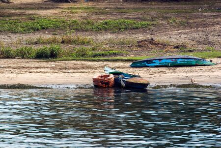 Two small fishing boats, typical of the Nile river, one on the shore of the river and the other on dry land with the keel up. Both in very poor condition of painting Stock Photo