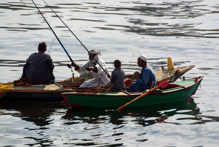 Nile river, near Aswan, February 16, 2017: Two small fishing boats typical of the river with fishermen with reeds and dressed in djellaba. One of them a child