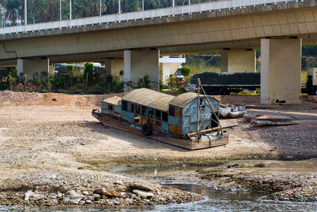 Metal barge of the Nile river in Egypt, stranded on the river bank under a bridge and ready for its demolition