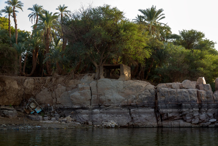Vertical rocky banks of the Nile river in Egypt with the shore full of vegetation and a small enclosure for the prayer of the Muslims. An old concrete mixer lying on the shore 写真素材
