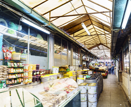 Porto, Portugal. August 12, 2017: Central hall of the market called Do Bolhao with stalls of olives and nuts and transparent roof very dirty