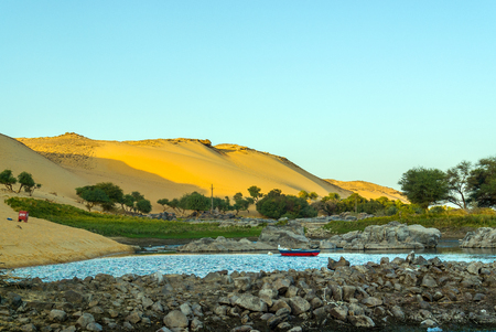 Dunes of the Sahara desert next to the Nile River in the evening, with lights and shadows. In the foreground a small lake with a boat and green vegetation Stock Photo