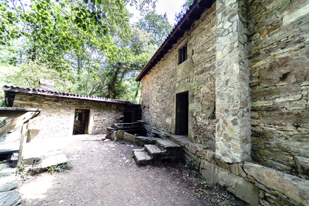 Courtyard and facade of an ancient rural stone house in Galicia, Spain.