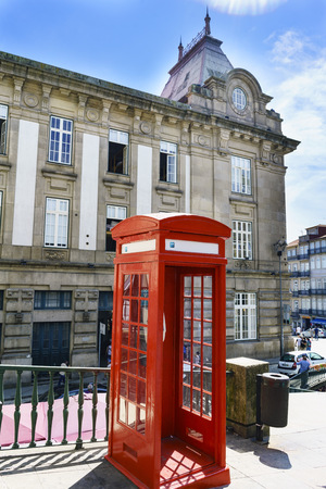 Porto, Portugal. August 12, 2017: Typical red telephone booth located in the square called Almeida Garret in the center of town