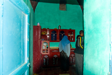 Cairo, Egypt February 18, 2017: Kitchen of a Nubian house with a woman with Hijab cooking in a kitchen with poor furniture painted red and polychrome