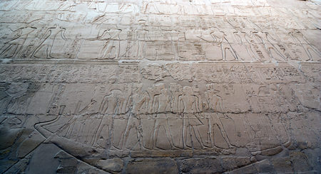 Wall of the karnak temple in Egypt in the hypostyle hall with hieroglyphics and an image of the sacred boat of the god Horus from Egyptian mythology with people on board