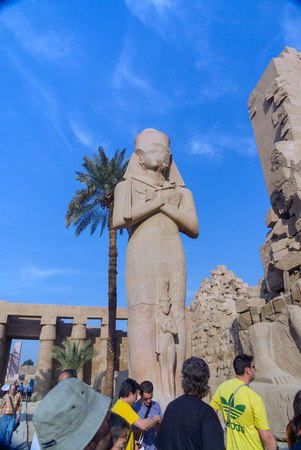 Luxor, Egypt. February 20, 2017: Statue of an Egyptian deity inside the karnak temple in the hypostyle hall with another small one stuck in front and tourists visiting the temple