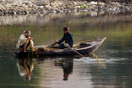Rio Nilo, near Aswnm, Egypt, February 21, 2017: Two Egyptian fishermen in a small boat fishing, one of them crouched in the stern and the other paddling Editorial