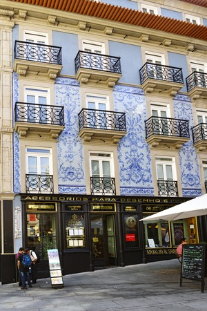 Porto, Portugal. August 12, 2017: Typical house facade decorated with blue tiles in the center of the city on the street called Santo Domingo with a shop with green wood facade Editorial