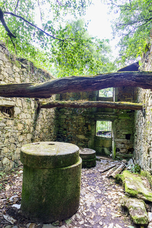 Grinding wheel and interior of a ruined stone mill in Galicia, Spain