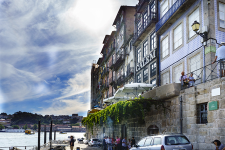 Porto, Portugal. August 12, 2017: Houses located on the banks of the estuary of the river Douro with terraces of bars and people drinking and walking