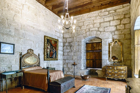 Guimaraes, Portugal. August 14, 2017: Medieval bedroom in the palace of the Dukes of Braganza with bed with polychrome headboard, pictures on the walls and medieval furniture. With stone walls and wooden roof Editorial