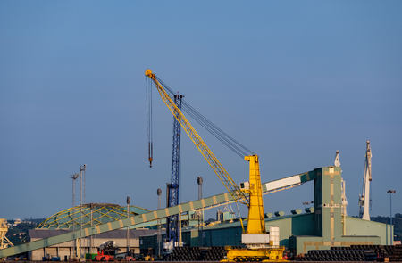 Heavy crane and buildings and industrial warehouses in port facilities Stock Photo