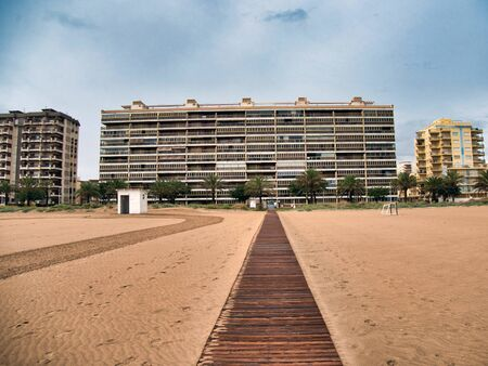 Modern buildings next to the beach with a wooden walkway leading to them on a cloudy and rainy day in Gandia, Valencia 스톡 콘텐츠